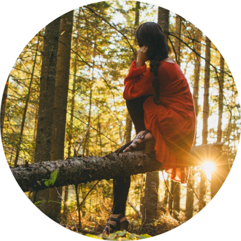 Frau sitzt im Wald auf einem Ast